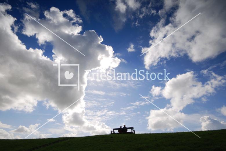 Mensen op bankje van zeedijk - FrieslandStock