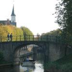Wandelaars over poort in Sloten - FrieslandStock