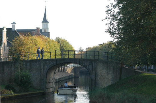 Wandelaars over poort in Sloten - FrieslandStock